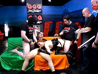 Queer redhead in latex gangbanged by a big group of guys